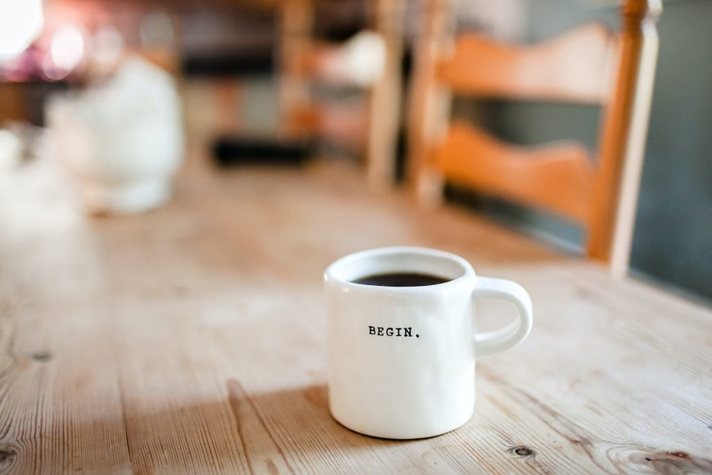"Coffee cup on long wood table that says ""Begin."""